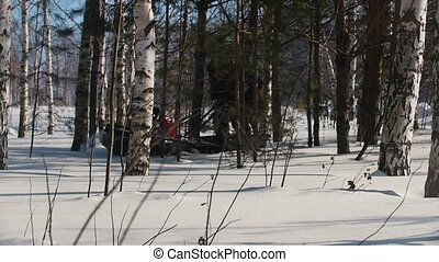 Man maneuvering on mini snowmobile on deep snowdrifts in the forest between the trees