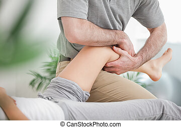 Man manipulating the leg of a woman while she is lying in a...