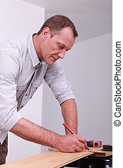 Man marking a floorboard with a pencil