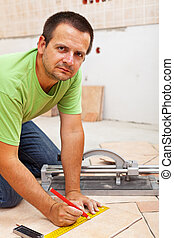 Man marking and cutting ceramic floor tiles