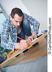 Man marking position on floorboard