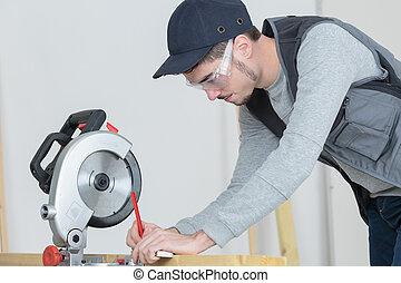 Man marking wood to cut with circular saw