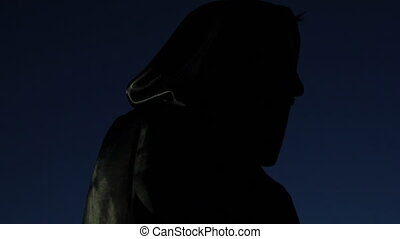 Man masked in terror in raincoats turning in darkness