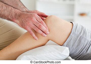 Man massaging a lying woman's knee