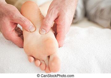 Man massaging a woman's foot