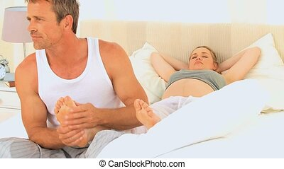 Man massaging feet of his pregnant