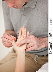 Man massaging the thumb of a woman