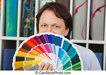 Man matching paint and carpet colours standing in front of...