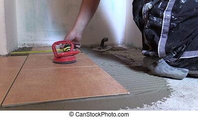 man measure tile floor - man measure with centimeter left...