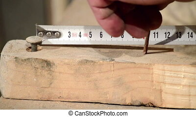 man measuring a wooden block and Hammering Nail into Wood
