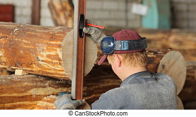 Man measuring a wooden post on the level.
