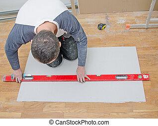 Man measuring and cutting gypsum plasterboard
