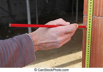 Man measuring brick wall