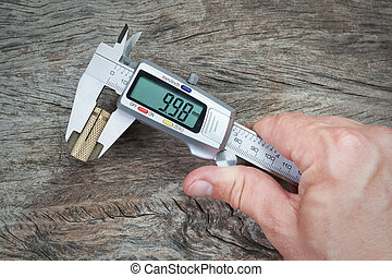 Man measuring caliper detail on a wooden background. Close-up.
