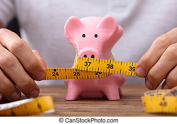 Man Measuring Piggybank With Measure Tape