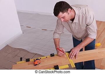 Man measuring plank of laminate flooring