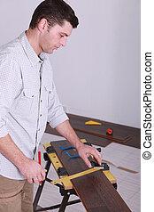 Man measuring plank of wood