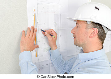 Man measuring plans pinned to wall