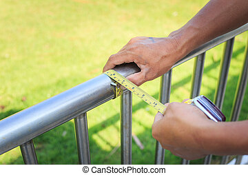Man measuring stainless steel railing with measuring tape.
