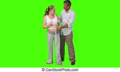 Chroma-key footage of a man measuring the belly of his pregnant woman