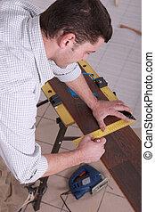 Man measuring wood flooring
