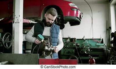 Man mechanic repairing a car in a garage. - Handsome man...