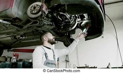 Man mechanic repairing a car in a garage. - Mature man...