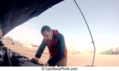 man mechanic repairing auto car breakdown engine turns key...