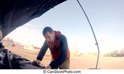 man mechanic repairing auto car breakdown engine turns key