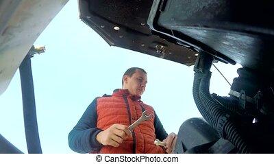 man mechanic repairing car auto breakdown engine turns key