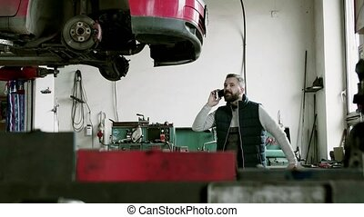 Man mechanic with smartphone repairing a car in a garage.