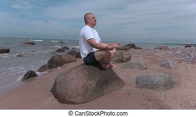 Man meditates by the sea