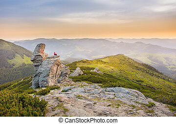man meditates on a rock in the mountains.