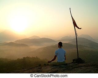 man meditating at su - man meditating on hilltop near flag...