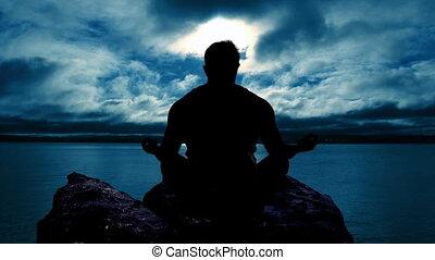 Man meditating at Sunset - Man doing yoga at Sunset
