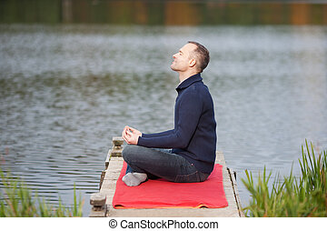 Man Meditating In Lotus Position On Pier Against Lake -...