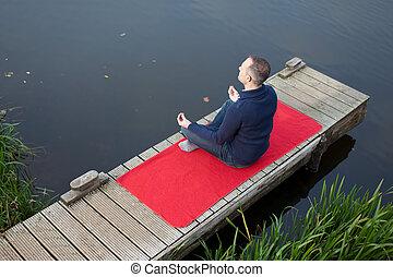 Man Meditating In Lotus Position On Pier