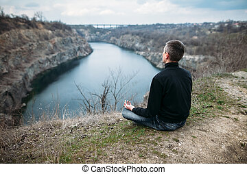 Man meditating on rocky cliff with river view