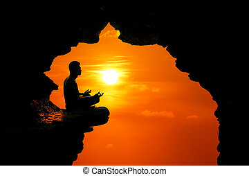 Man meditation and praying in the cave on the high cliff at sunset red sky