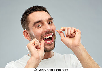 man, met, dentale floss, schoonmakende tanden, op, grijs