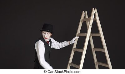 Man mime climbs the ladder up, looks around, running away from an imaginary beast