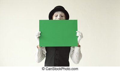 man mime holding a green billboard