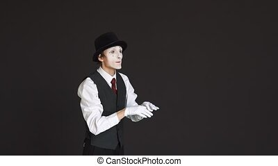 Man mime in virtual reality on a black background. He turns the pages, surfing the Internet