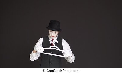 man MIME plays with a clothes hanger on a black background
