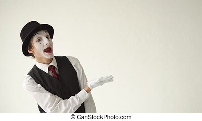 man MIME shows his hand at something. The concept of advertising, on a white background