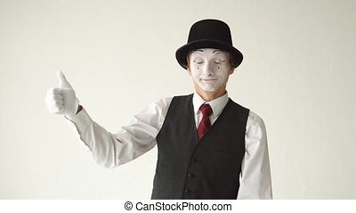 man MIME shows thumbs up and thumbs down, looking at the camera on white background