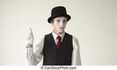 man mime standing on white background and looking to the...