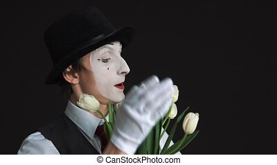 man mime with a bouquet of flowers on a black background