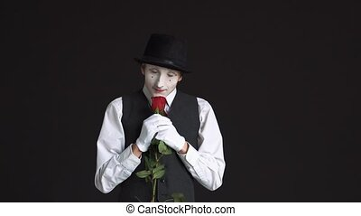 man mime with a red rose on a black background. He sniffs the flower and dreams of a date with a woman