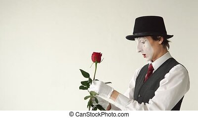Man mime with a red rose on a white background. MIM fingers pricked on the thorn of a rose